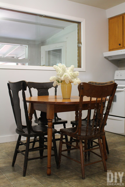 Round kitchen table with mixed matched antique chairs.