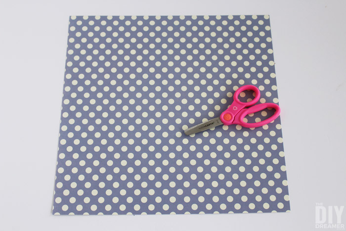 Cut the scrapbook paper in half.
