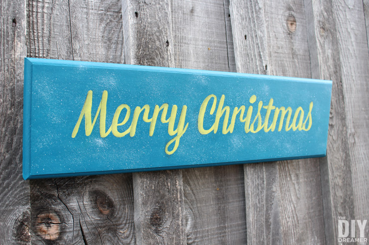 Hand painted wooden Merry Christmas wall plaque sign. This is part 1 of a two-part Merry Christmas sign DIY tutorial. Part 1 explains how to make the Merry Christmas sign and Part 2 demonstrates how to go from a pretty sign to a STUNNING Merry Christmas sign! Click through for the tutorial: thediydreamer.com