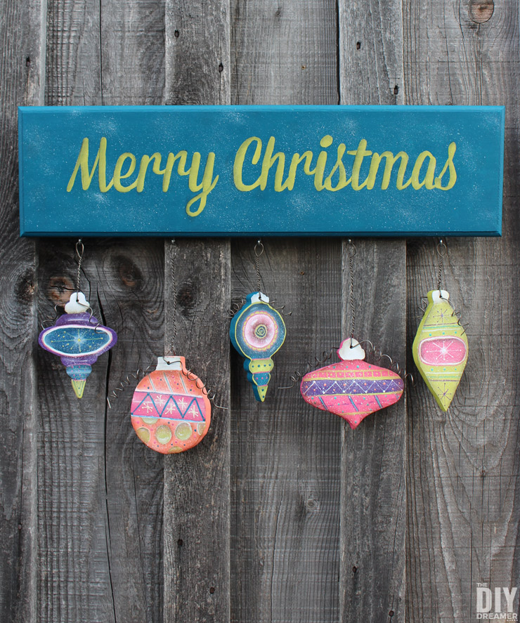Hand painted Merry Christmas Sign with Hanging Ornaments. This entire project was hand painted! A beautiful DIY Christmas sign using fun colors! Click through for the tutorial: thediydreamer.com
