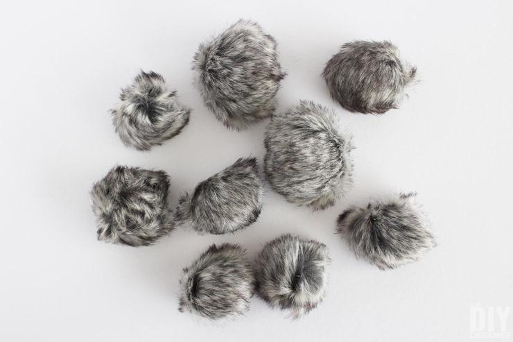 Grey faux fur pom poms.