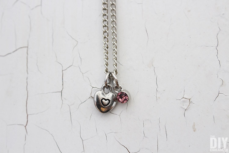 Super cute DIY Valentine Heart Necklace that costs less than $3 to make! These charm necklaces are easy to customize to please everyone.