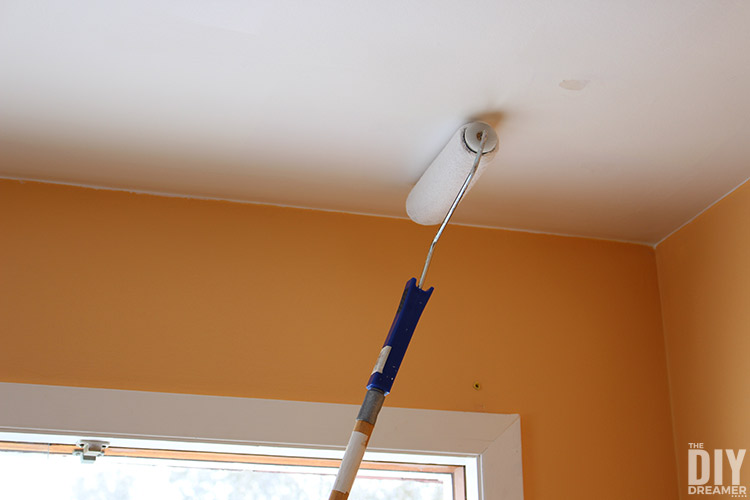 Use paint roller with long handle to paint the ceiling.