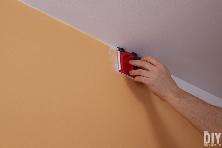 Using a paint edger to paint a teen bedroom wall