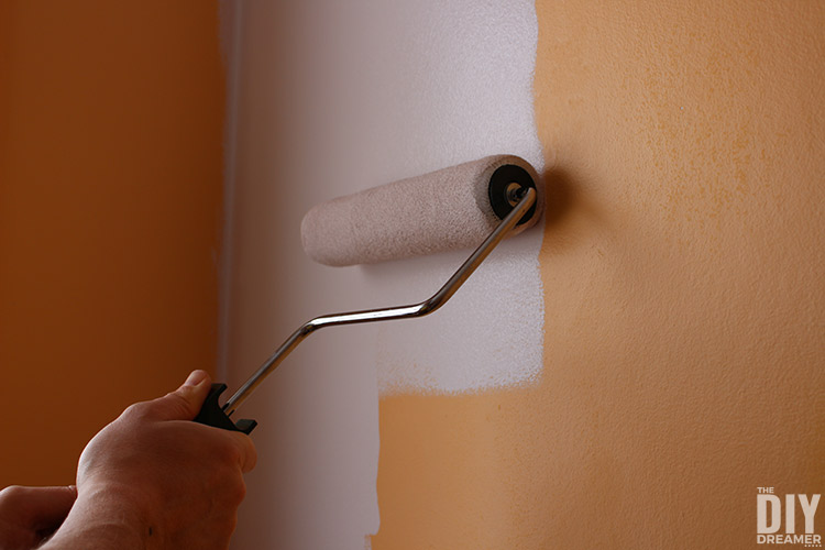 Using a paint roller to paint a wall