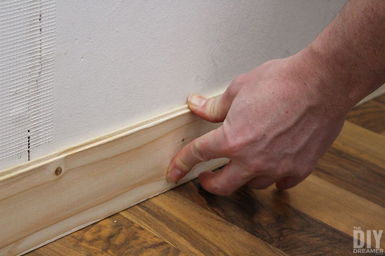 Press plank firmly to wall for glue to adhere.