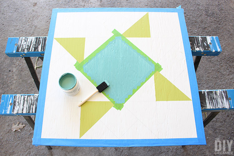 Painting barn quilt in blue and green.