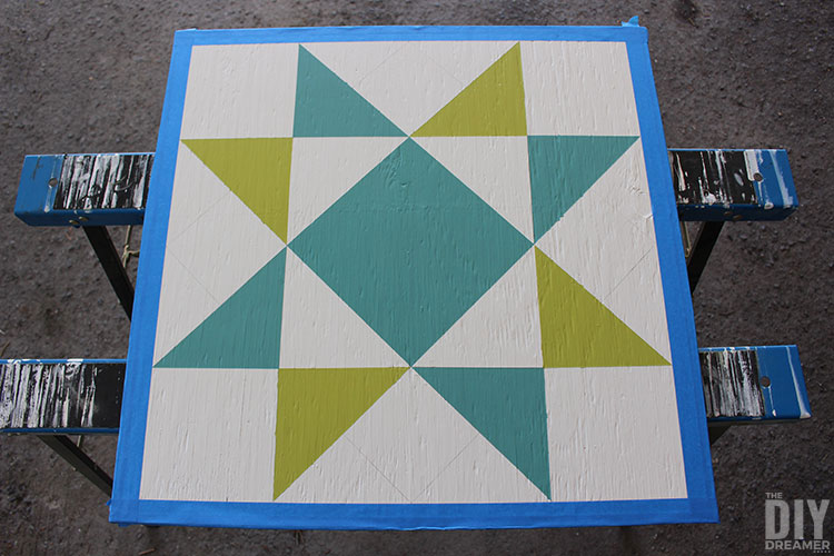 Barn quilt painted in blue and green.