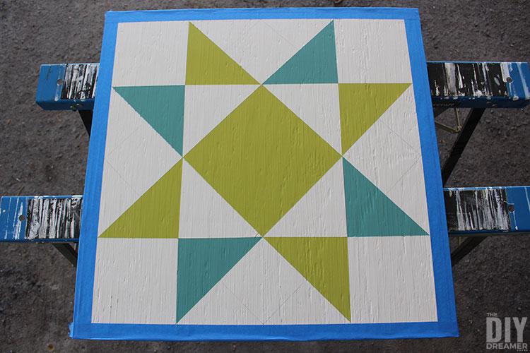 Barn quilt painted on plywood in green and blue.