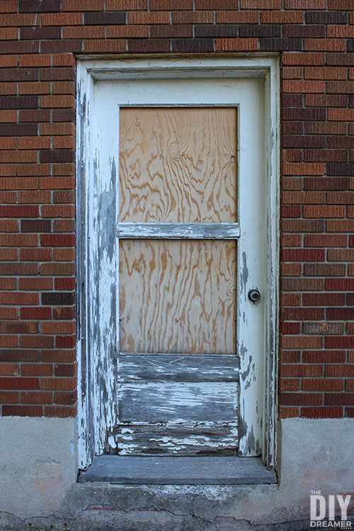 Old wood door with windows replaced with plywood.