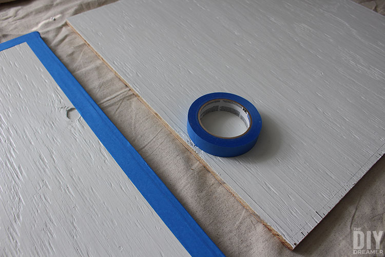 Place tape around the edge of the piece of plywood to make it square.