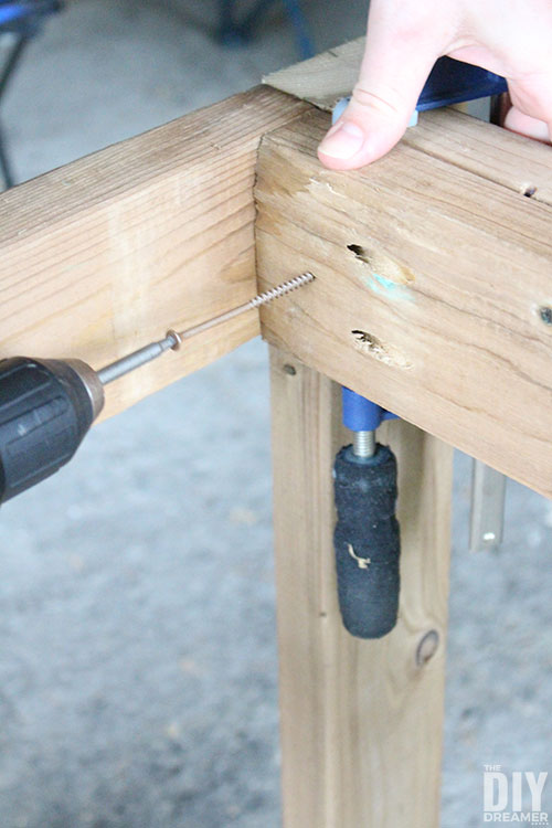 Add decking screws to attach the legs to the table frame.