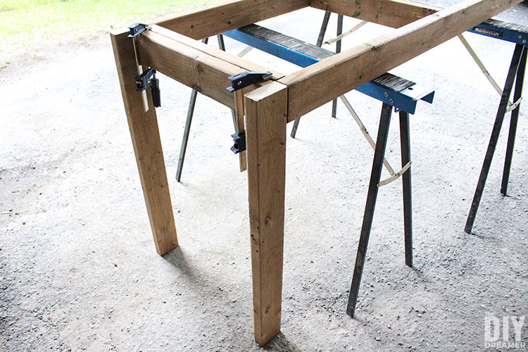 Use sawhorses and clamps to attach the legs to the table frame.