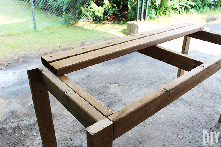 Placing the boards over the table base to create the tabletop.
