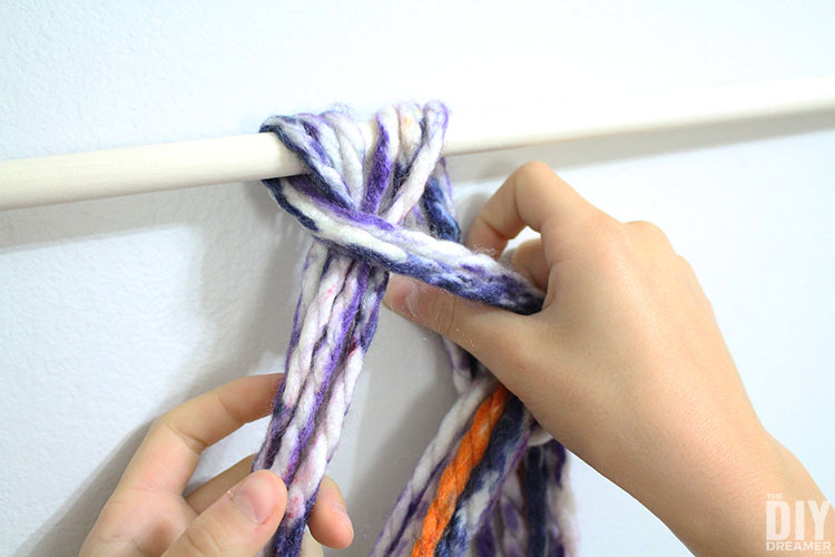 Place yarn strands into the loop and pull to tighten.