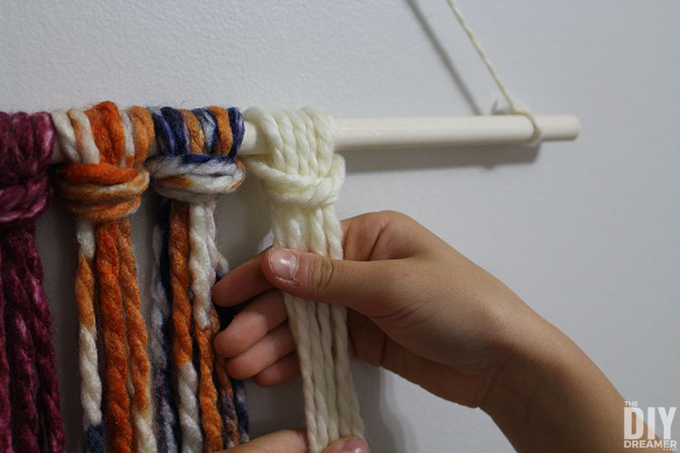 Yarn knots on the wood dowel.