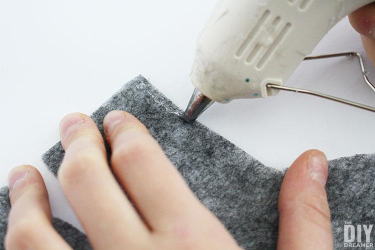 Hot glue edges of wool socks.