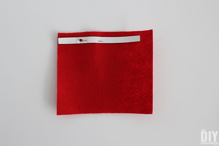 Small strip pinned on red felt.